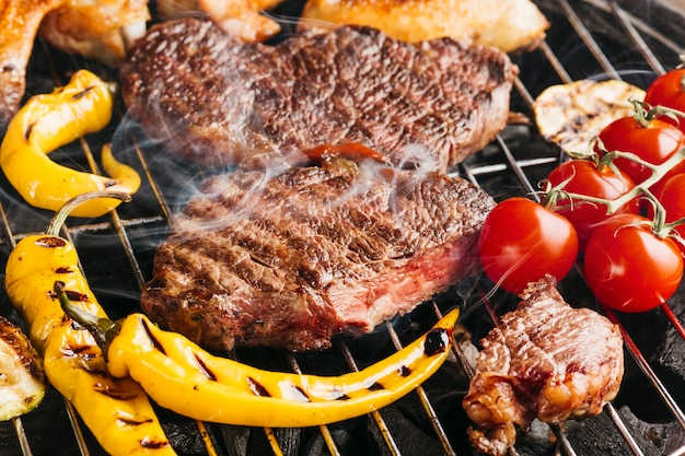 Tasty beef steaks on the grill with yellow chili and cherry tomato