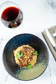 Вкусный стейк из говяжьего языка с грибами подается на пюре из овощей в стильной черной миске на мраморной тарелке