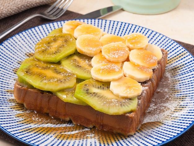 Tasty belgian waffle with caramel banana and kiwi