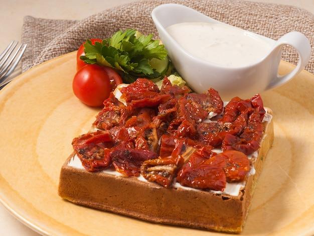 햇볕에 말린 토마토와 코티지 치즈를 곁들인 맛있는 벨기에 와플