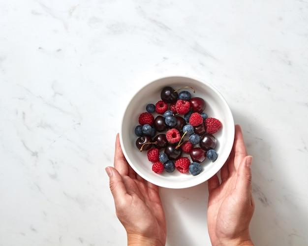 맛있는 딸기, 콘크리트 배경에 있는 여성의 손에 있는 세라믹 접시에 갓 딴 과일. 복사 공간이 있는 건강 식품의 개념입니다. 플랫 레이