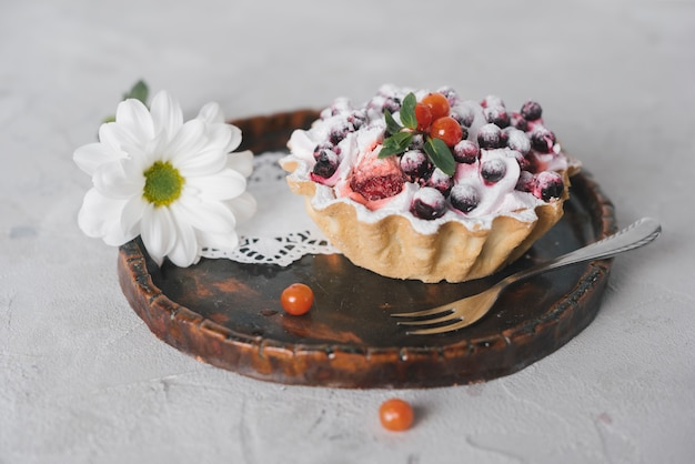 Tasty berries tart with fork and flower on round wooden tray