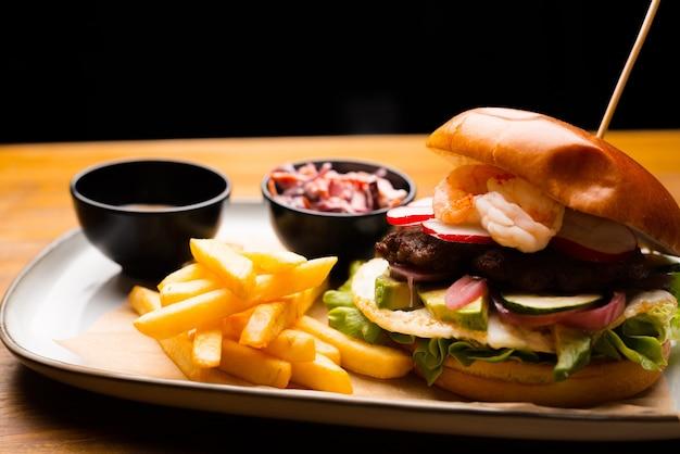 Вкусный большой гамбургер и немного картофеля с соусом на тарелке, на деревянном столе.