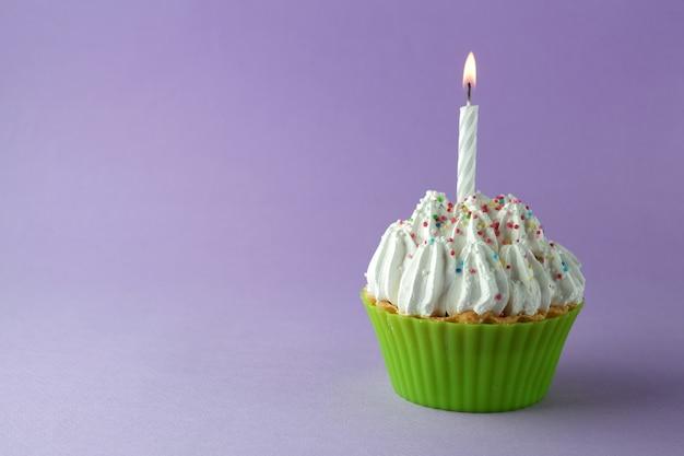 紫色の背景にキャンドルでおいしい誕生日ケーキ