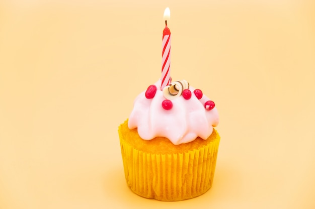 Tasty birthday cupcake with candle, on orange background.