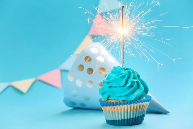Tasty birthday cupcake with sparkler and party hat on blue
