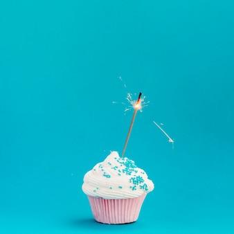 Tasty birthday muffin on blue background