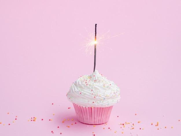 Tasty birthday muffin on pink background