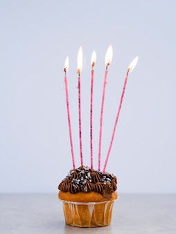 Tasty birthday muffin with long candles
