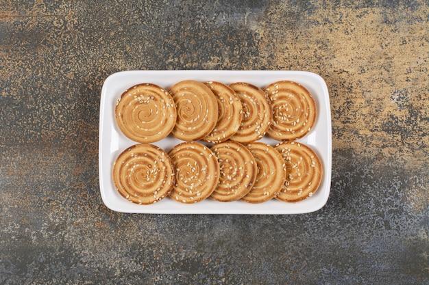 Вкусное печенье с кунжутом на белой тарелке.