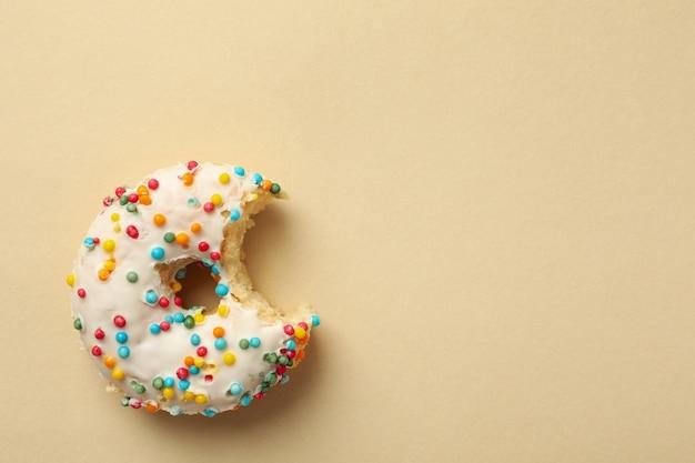 Tasty bitten donut on beige background, top view