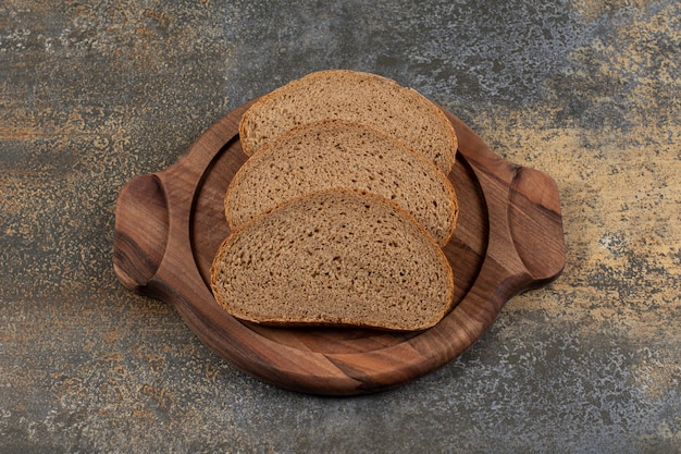 나무 보드에 맛있는 검은 빵 조각.