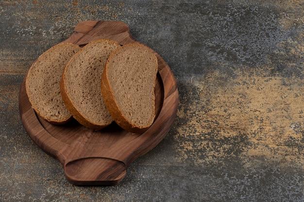 Tasty black bread slices on wooden board