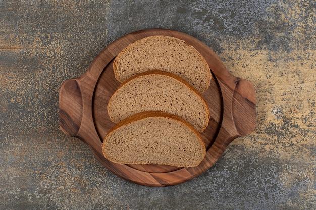 Gustose fette di pane nero su tavola di legno.