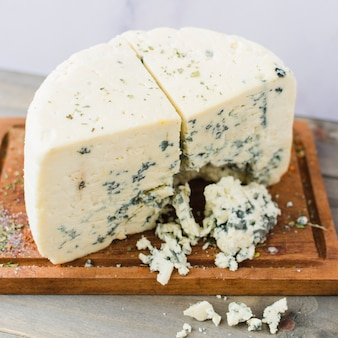 Tasty blue cheese slice on chopping board
