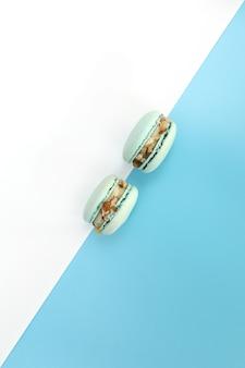 白と青の背景においしい青いフレンチマカロンまたはマカロン。カラージオメトリ。