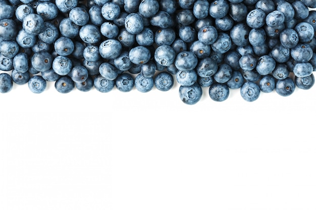 Tasty blueberries fruit are scattered on a white. frame