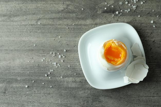 Tasty boiled egg on gray textured