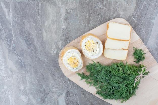 Вкусные вареные яйца на белом хлебе с зеленью на деревянной доске. фото высокого качества