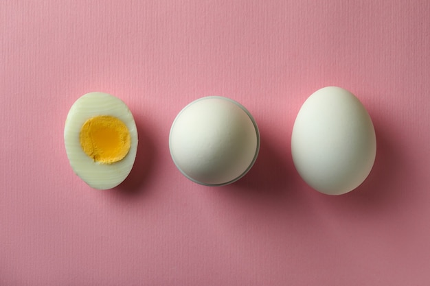 Tasty boiled eggs on pink