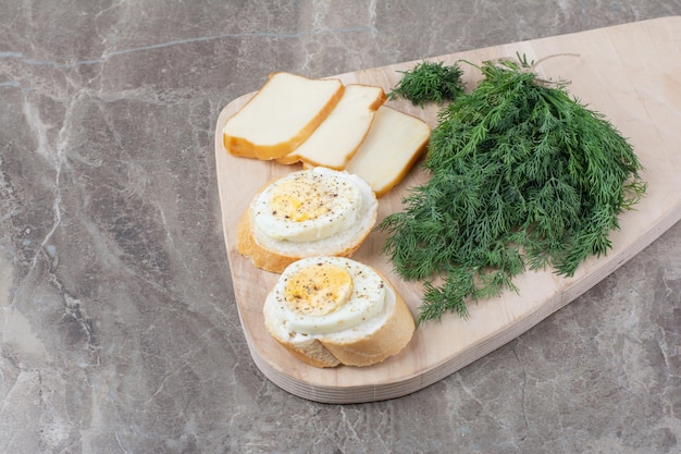 Tasty boiled eggs on white breads with greens on wooden board. high quality photo