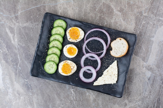 Tasty boiled eggs with spices and vegetables on dark plate. high quality photo