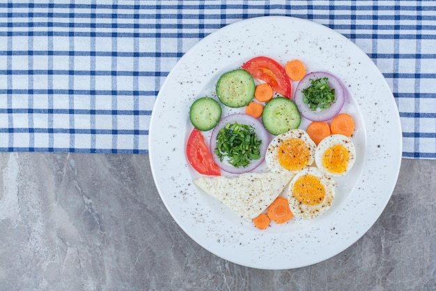 Tasty boiled eggs with spices and vegetables on tablecloth. high quality photo
