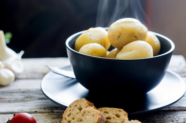 검은 그릇에 딜, 스파 슬리, 양파를 곁들인 맛있는 삶은 감자
