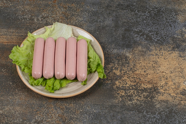 Вкусные вареные колбаски и салат на керамической тарелке.
