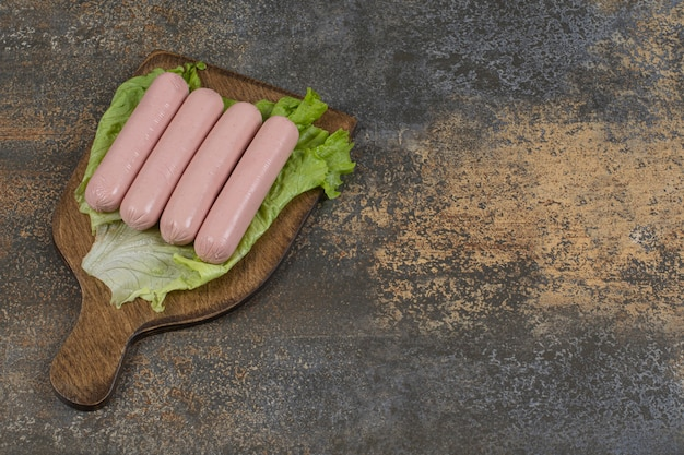 Tasty boiled sausages and lettuce on wooden board.