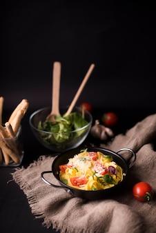 Вкусные макароны с отварными спагетти с листьями базилика и помидорами на мешочке с хлебными палочками и овощным салатом