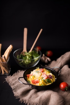 Tasty boiled spaghetti pasta with basil leaves and tomato on sack with bread sticks and veg salad
