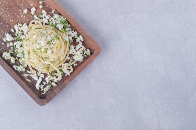 Вкусные отварные спагетти с тертым сыром на деревянной доске.