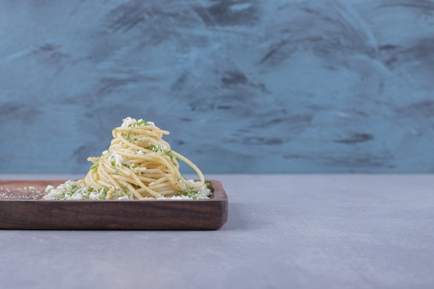 Tasty boiled spaghetti with grated cheese on wooden board.
