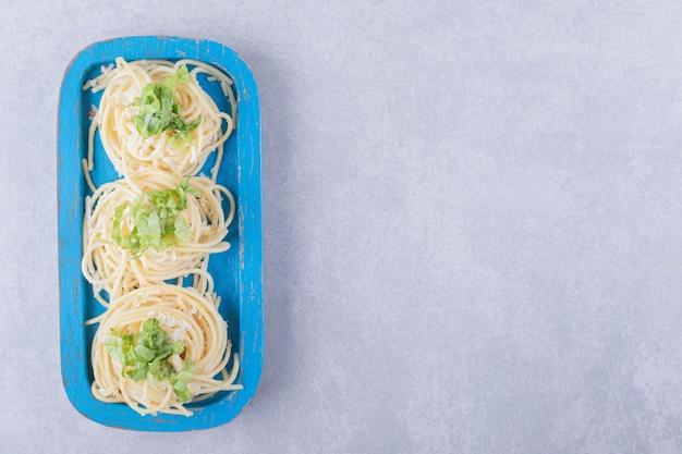 Spaghetti bolliti saporiti con i verdi sul piatto blu.