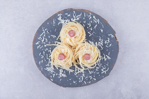 나무 조각에 소시지와 맛있는 삶은 스파게티.