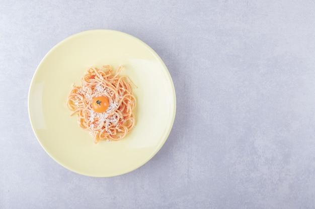 노란색 접시에 토마토와 맛있는 삶은 스파게티.