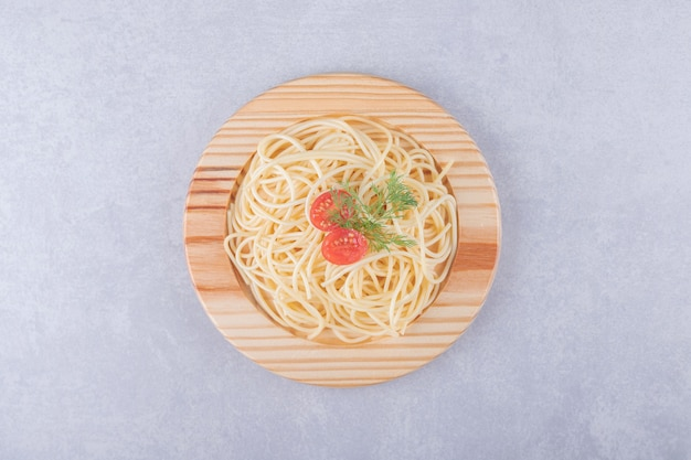 Tasty boiled spaghetti with tomatoes on wooden plate.