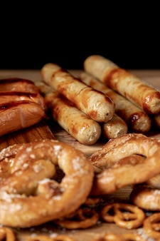 Tasty bratwurst with pretzels on a table