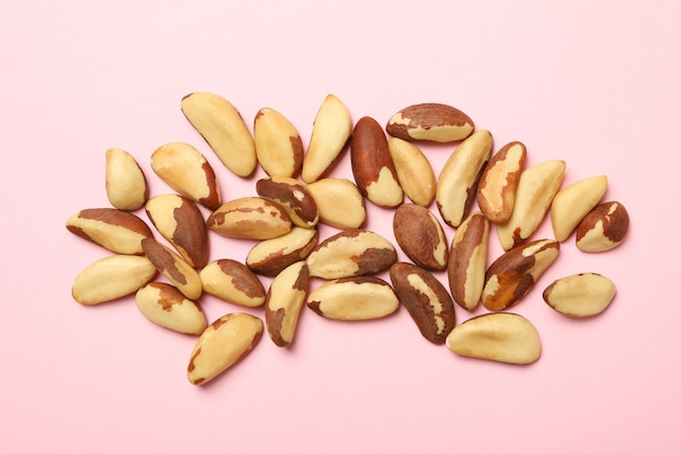 Tasty brazil nuts on pink background, top view