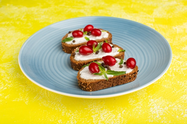 Tasty bread toasts with sour cream and dogwoods inside blue plate on yellow
