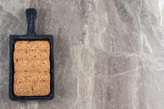 Tasty breadcrumbs on a board on marble.