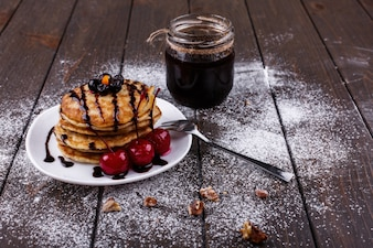 Tasty breakfast. Delicious pancakes covered with chocolate and cherries