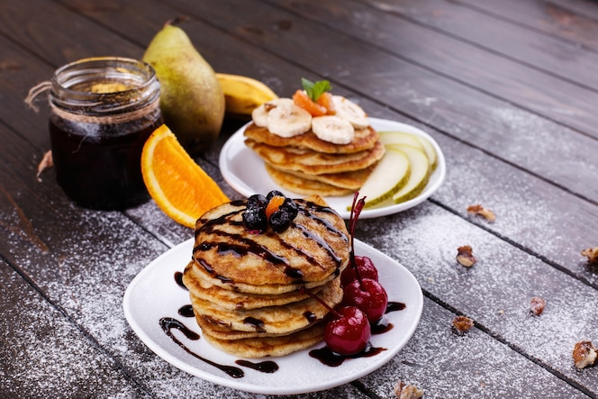 Tasty breakfast. delicious pancakes covered with chocolate, cherries, bananas and pears