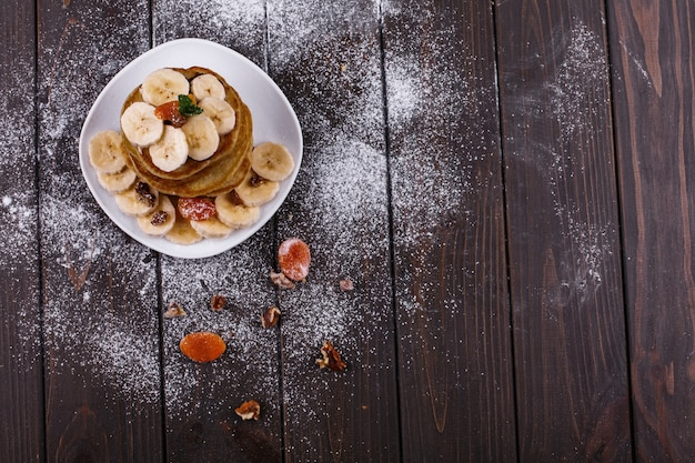 Tasty breakfast. delicious puncakes with bananas, nuts and mint served on white plate