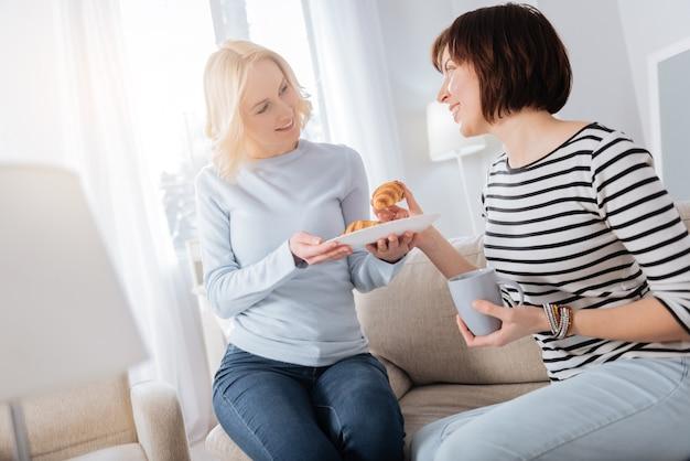 맛있는 아침. 맛있는 아침 식사를 함께하면서 서로를보고 웃고 기쁘게 긍정적 인 좋은 여성