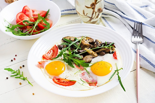 Tasty  breakfast - fried eggs, forest mushrooms, tomatoes and arugula. lunch food.