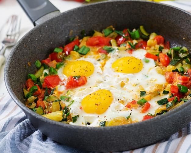 Tasty breakfast. fried eggs with vegetables. shakshuka.