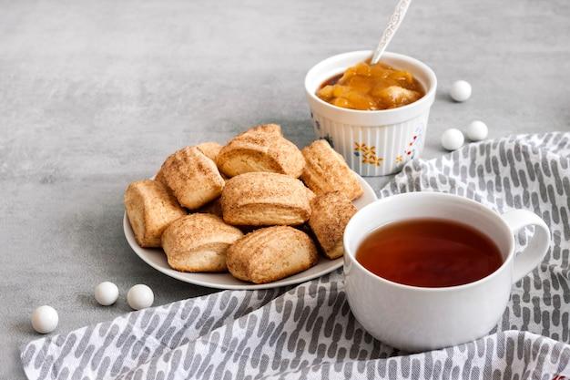 おいしい朝食。自家製の甘いシナモンクッキーとお茶。表面にアップルのコンフィチュール。コピースペース