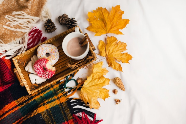 Вкусный завтрак в постели на деревянном подносе с чашкой какао, корицей, печеньем и глазированными пончиками.